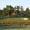 A view over the water of a green and the clubhouse in background at Olde Sycamore Golf Plantation